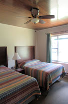Shamrock Motel and Cottages Long Lake NY Motel room view with to double beds, ceiling fan and beautiful wainscoat ceiling, large picture window.